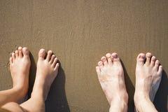 Man- och kvinnafot som står på den sandiga bruna stranden Arkivfoton