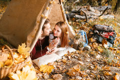 Man- och kvinnafotvandrare som campar i höstnatur Lyckliga barnparfotvandrare som campar i tält Royaltyfria Bilder