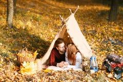 Man- och kvinnafotvandrare som campar i höstnatur Lyckliga barnparfotvandrare som campar i tält Arkivfoton