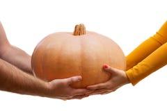 Man- och kvinnahänder rymmer en stor pumpa Royaltyfri Bild