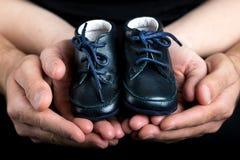 Man- och kvinnahänder som rymmer ett par av, behandla som ett barn skor Arkivbilder
