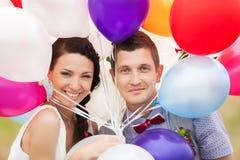 Man- och kvinnainnehavet räcker in många färgrika latexballonger Arkivfoto