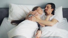 Man- och kvinnapar ligger i säng som kramar samtal tycka om läggdags lager videofilmer