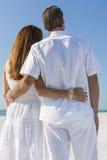 Man- och kvinnapar som omfamnar på stranden Arkivfoton