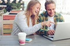 Man- och kvinnasammanträde i gatakafé med bärbara datorn och gladlynt och le par som diskuterar plan arkivfoton