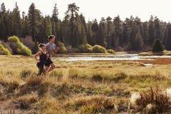 Man- och kvinnaspring i naturen nära en sjö, sidosikt royaltyfria foton