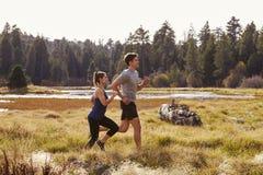 Man- och kvinnaspring i naturen nära en sjö, slut upp royaltyfri foto
