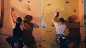 Man- och kvinnastart som ska klättras på en vägg, slut upp arkivfilmer