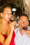 Man- och kvinnatasking wine i källare Arkivfoton