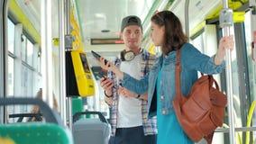 Man och kvinnaturist som offentligt använder transport för telefonköpbiljetter stock video