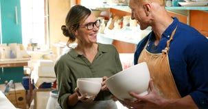 Man och kvinnlig keramiker som rymmer keramiska bunkar 4k stock video