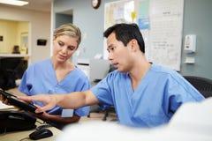 Man och kvinnlig sjuksköterskaWorking At Nurses station Arkivfoton