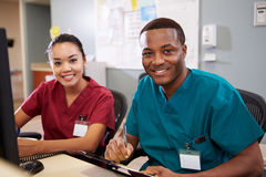 Man och kvinnlig sjuksköterskaWorking At Nurses station Arkivbild