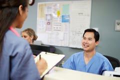 Man och kvinnlig station för sjuksköterskaIn Discussion At sjuksköterskor Arkivfoton