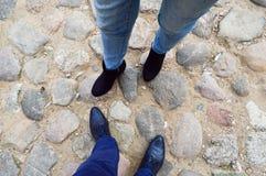 Man och kvinnliga ben i läderskor, kängor på en stenväg av stora kullerstenstenar mitt emot de grönska för abstraktionbakgrundsge royaltyfri foto