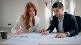 Man och kvinnliga finansiella konsulenter som diskuterar aktuellt marknadsläge lager videofilmer