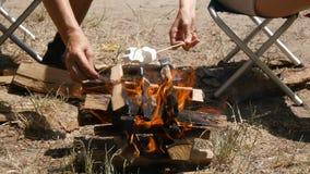 Man och kvinnliga händer som grillar marshmallower på en brand N?rbild Fotvandra lopp, grönt turismbegrepp Sund aktiv lager videofilmer