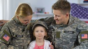 Man och kvinnliga soldater som kramar dottern i det militära locket som ler på kamera arkivfilmer