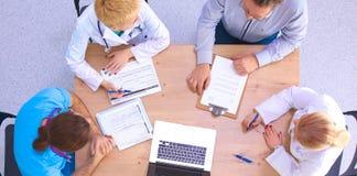 Man- och kvinnligdoktorer som arbetar på rapporter i medicinskt kontor royaltyfri bild
