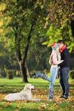 Man och kvinnligt kyssa i en parkera och en hund som håller ögonen på dem Royaltyfria Foton