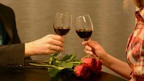 Man och kvinnligt rosta med exponeringsglas av rött vin på restaurangtabellen med röda rosa blommor