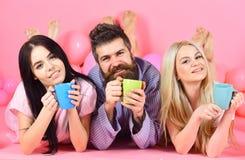 Man och kvinnor i inhemsk kläder, pyjamas Mannen och kvinnor, vänner på lyckliga framsidor lägger, rosa bakgrund Threesomen koppl Arkivfoton