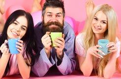 Man och kvinnor i inhemsk kläder, pyjamas Threesomen kopplar av i morgon med kaffe Vänner i sängbegrepp Man och kvinnor Arkivfoto