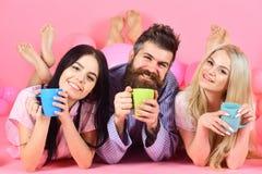 Man och kvinnor i inhemsk kläder, pyjamas Vänner som dricker kaffe i säng Vänner i sängbegrepp Man och kvinnor, vänner Royaltyfri Foto