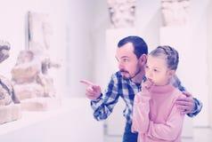 Man och liten flicka som ser forntida statyer Arkivbild