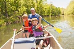 Man och pojkar som paddlar kanoten Royaltyfri Foto