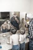 Man och pojkar som rakar deras framsidor Royaltyfri Fotografi