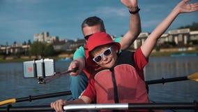 Man och pojke som kayaking och gör videoen stock video