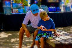 Man och pojke som ser kortleken royaltyfri foto