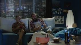 Man och pojke som spelar videogamen tillsammans stock video
