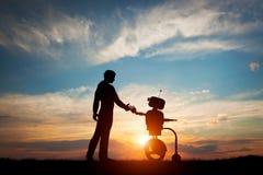 Man och robotmöte och handskakning Begrepp av framtida växelverkan med konstgjord intelligens Arkivfoto