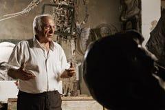 Man och skulpturhuvud Arkivfoto