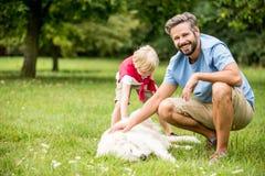 Man och son som daltar hunden royaltyfri bild