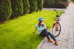 Man- och stadsrullningen cyklar, miljövänlig transport Härligt ungt caucasian sammanträde för kvinnaarbetare som vilar på gren royaltyfri foto