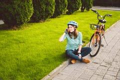 Man- och stadsrullningen cyklar, miljövänlig transport Härligt ungt caucasian sammanträde för kvinnaarbetare som vilar på gren royaltyfri bild