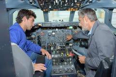 Man och student i cockpitflygplan royaltyfria bilder