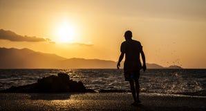 Man och vågor som plaskar på en härlig solnedgång Royaltyfri Fotografi