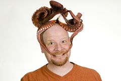 Man with an octopus on his head. An odd, bald man with a dead octopus on his hand and in his mouth Royalty Free Stock Photo