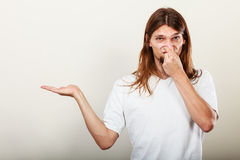 Man with odor of sweat. Expression of very bad smell. Young long haired sweaty man making hand gesture open empyt hand for product. Sweating concept Stock Image