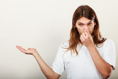 Man with odor of sweat. Expression of very bad smell. Young long haired sweaty man making hand gesture open empyt hand for product. Sweating concept Royalty Free Stock Photos