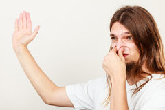 Man with odor of sweat. Expression of very bad smell. Young long haired sweaty man making hand gesture. Sweating concept royalty free stock photo