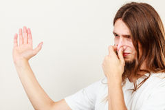 Man with odor of sweat. Expression of very bad smell. Young long haired sweaty man making hand gesture. Sweating concept stock photography