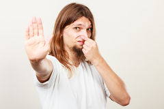 Man with odor of sweat. Expression of very bad smell. Young long haired sweaty man making hand gesture. Sweating concept Stock Photos