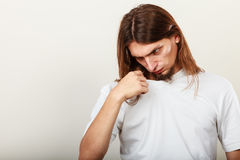 Man with odor of sweat. Expression of very bad smell. Young long haired sweaty man making hand gesture. Sweating concept Stock Images