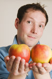 Man offer two apples. Young man offer two apples to the camera Royalty Free Stock Photos