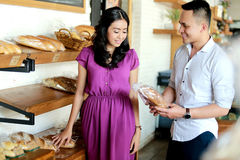 Man offering bread to his girlfriend at bakery shop Royalty Free Stock Photo